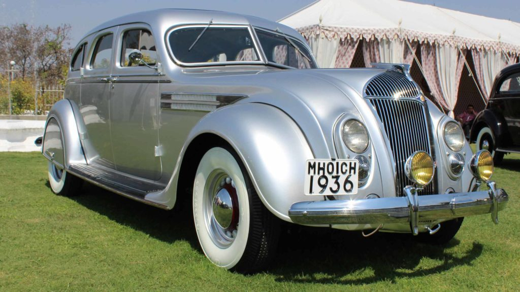 Front view of the sleek car with sloping front radiator grille and inbuilt headlights in view, Photo Credit: Karl Bhote