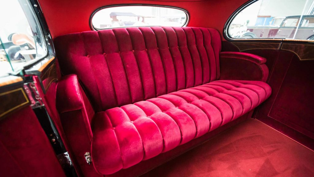 View of the plush interiors of Hispano Suiza upholstered in rich maroon velvet; Photo Credit: https://www.artcurial.com/en/lot-1937-hispano-suiza-j12-gurney-nutting-3279-28