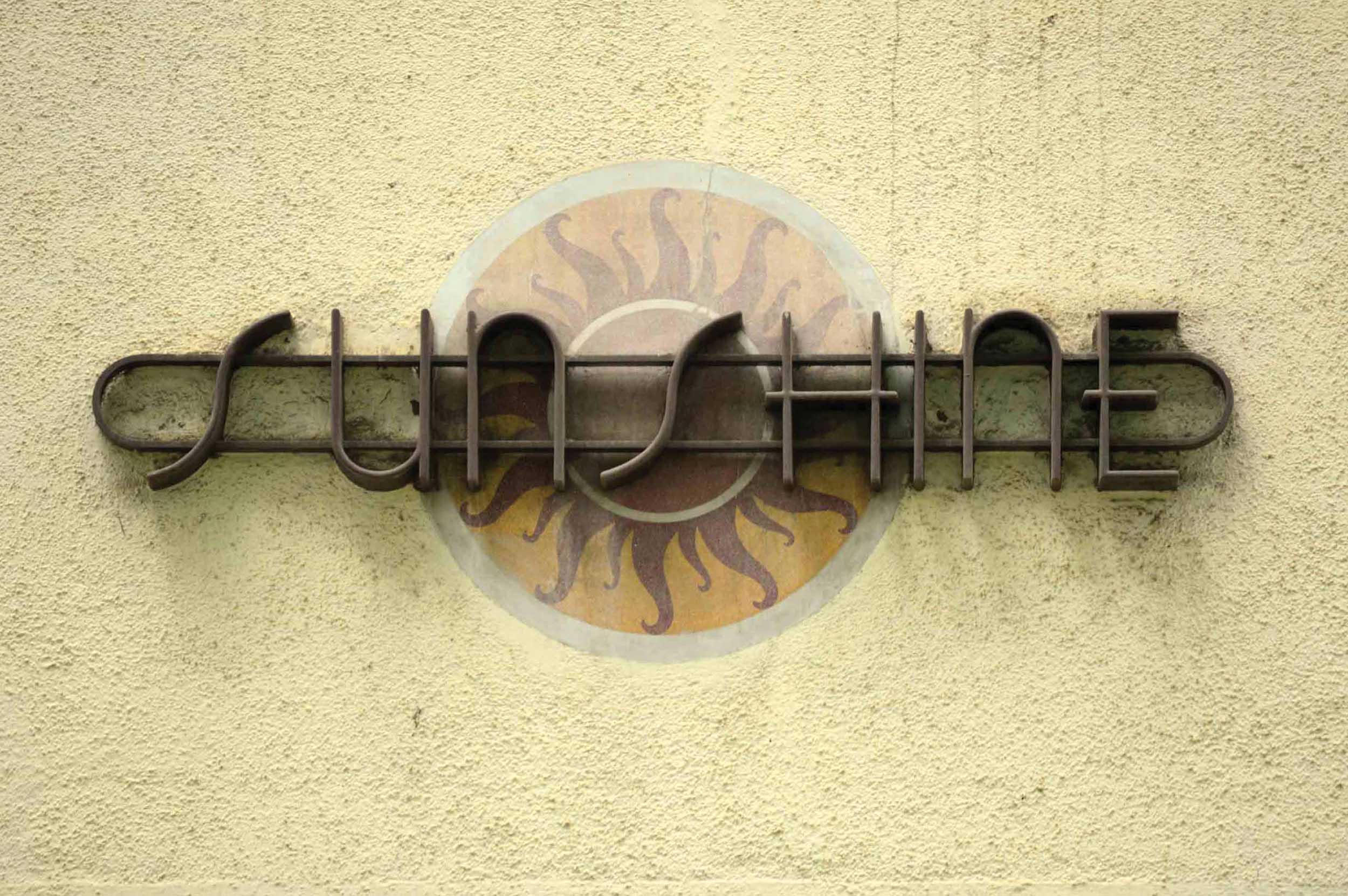 Detailed view of architectural lettering and plaster work on Sunshine, Oval Maidan