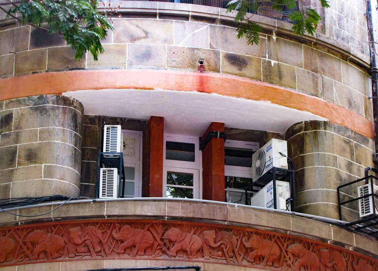 Façade of Lakshmi Building with chhajas and carved elephants on red sandstone panels. Master, Sathe & Bhuta. 1936–1938. Bombay, India. Source: Art Deco Mumbai