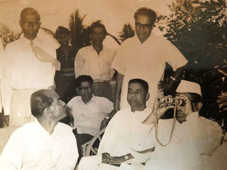 This photograph was taken at Pansare's (seated in the far-left corner) home and studio in Bandra (E). Here, Shri Balasaheb Desai is using an inverted binocular to view the whole statue of Chhatrapati Shivaji Maharaj; Source: Pansare Family Archive