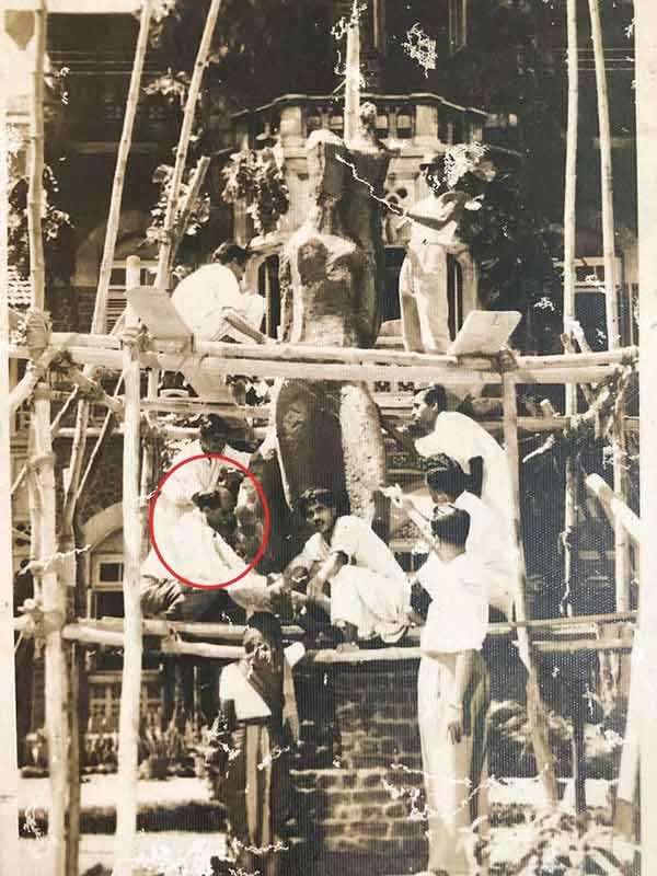 The before completion picture of the J.J. School of Art installation by Pansare. Seen (in circle - dark trousers and light shirt) kneeling at the first level of scaffolding in the lower-left corner; Source: Pansare Family Archive